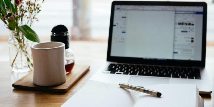 电脑文字处理机,前面放一叠纸,旁边放一杯咖啡